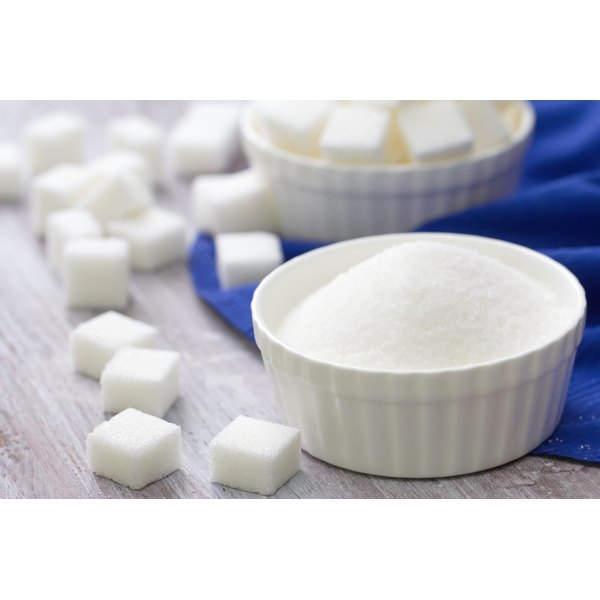 Simple sugar in a bowl next to sugar cubes.