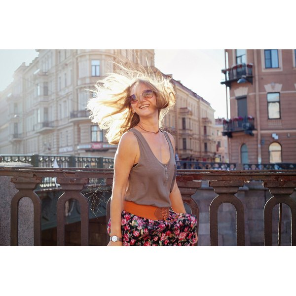 The wind blows a woman's hair against a city background.