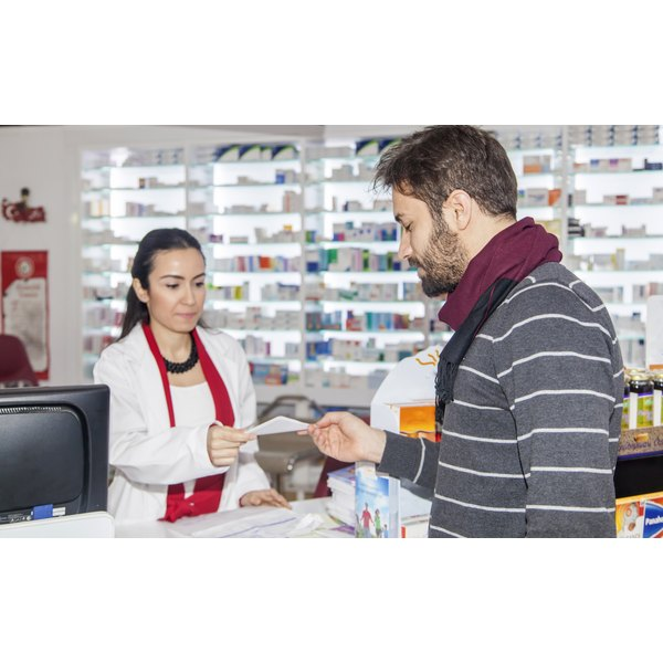 Young man giving pharmacist a prescription