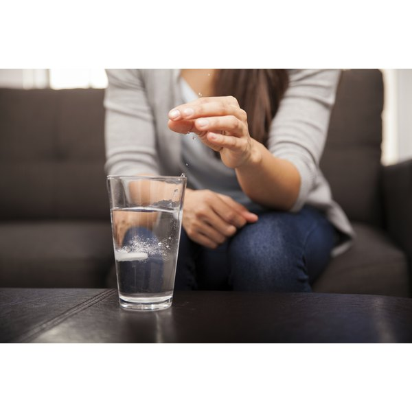 A woman is dissolving a supplement pill in a glass of water.