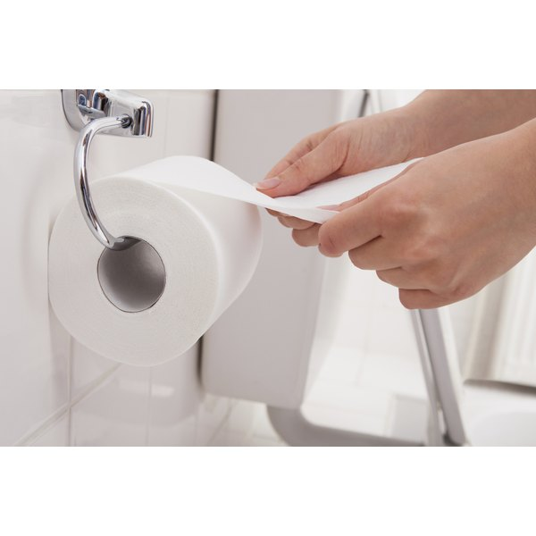 Woman's hands pulling toilet paper off a roll.