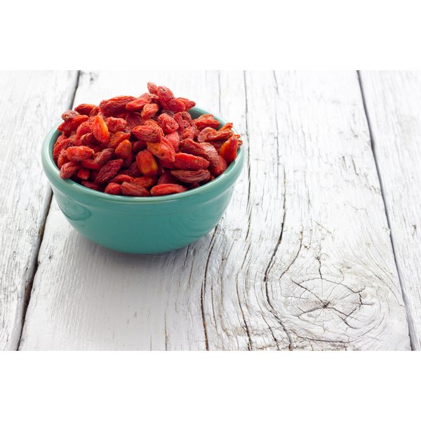 Dried goji berries, in a bowl on a wooden table.