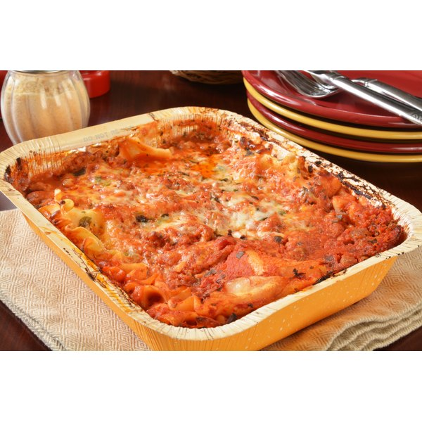 A cooked lasagna sits in an oven roasting dish on a cutting board in a kitchen.