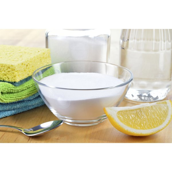 A dish of baking soda and a lemon wedge on a table with other natural cleaning products.