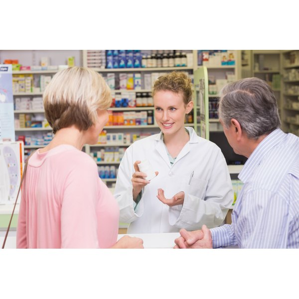 A pharmacist is talking to two clients.