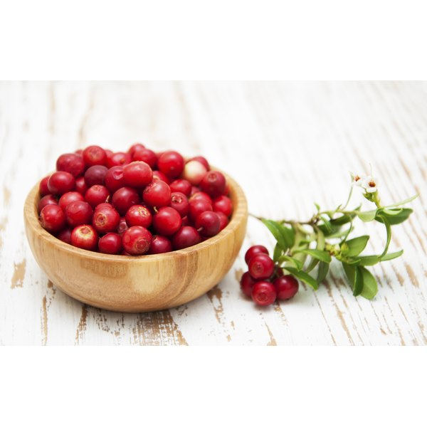 Fresh cranberries in a wooden bowl on a table.