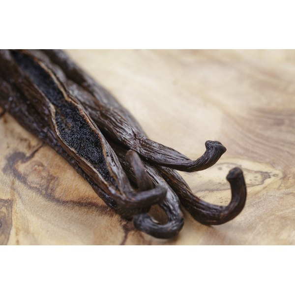An open vanilla bean on olive wood.