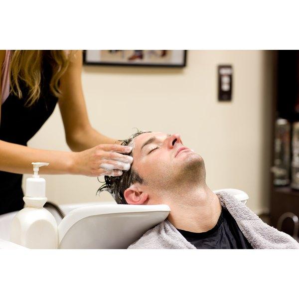 A man is getting his hair shampooed.