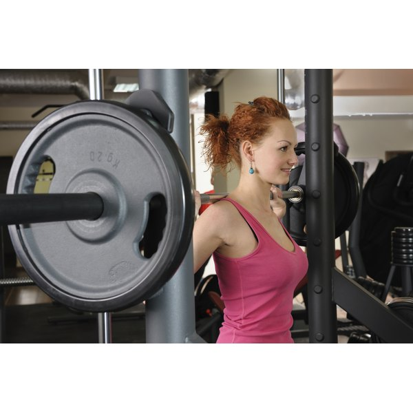 A young woman doing squats with a barbell.