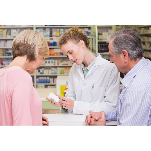 A pharmacist is reviewing medication with her clients.