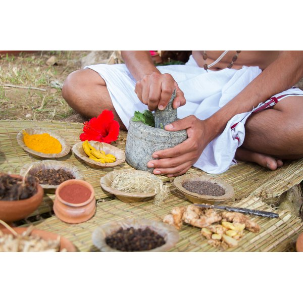 A man grinding Ayurvedic herbs with a mortar and pestle.