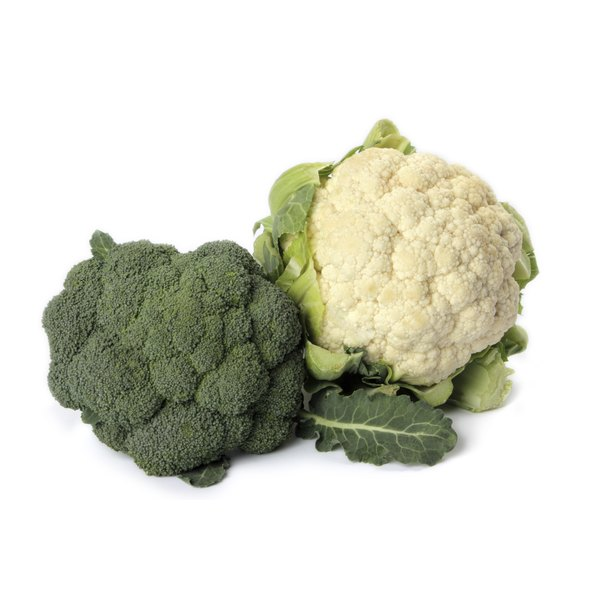 Heads of cauliflower and broccoli sit on a white counter.