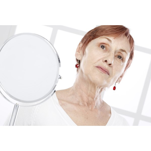 Senior woman looking at her neck in a mirror