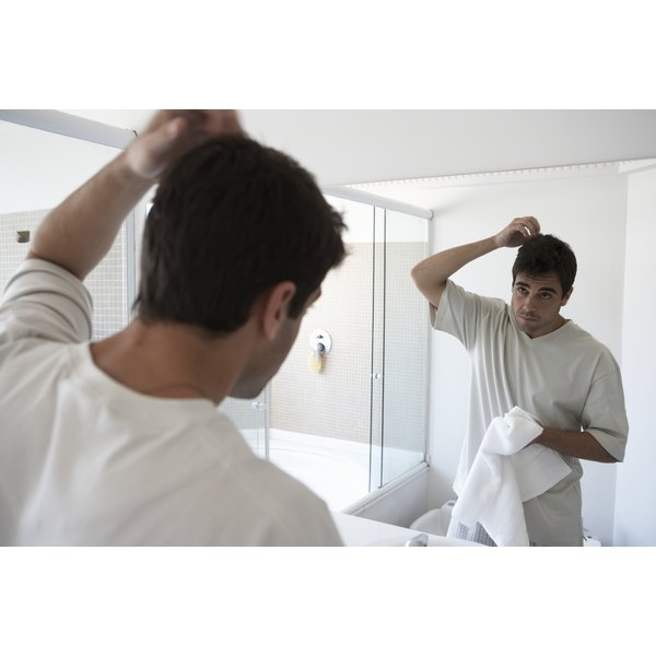 A man looking at his hair in the mirror.