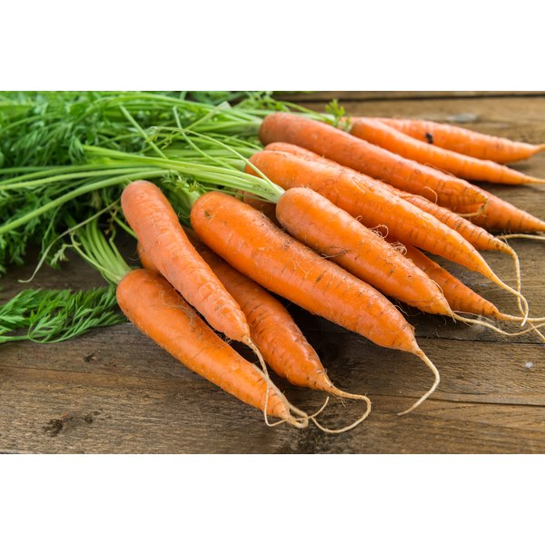 A bunch of carrots on a wooden table.