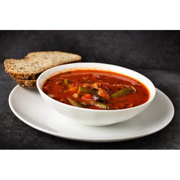 A bowl of vegetable soup and a slice of bread.