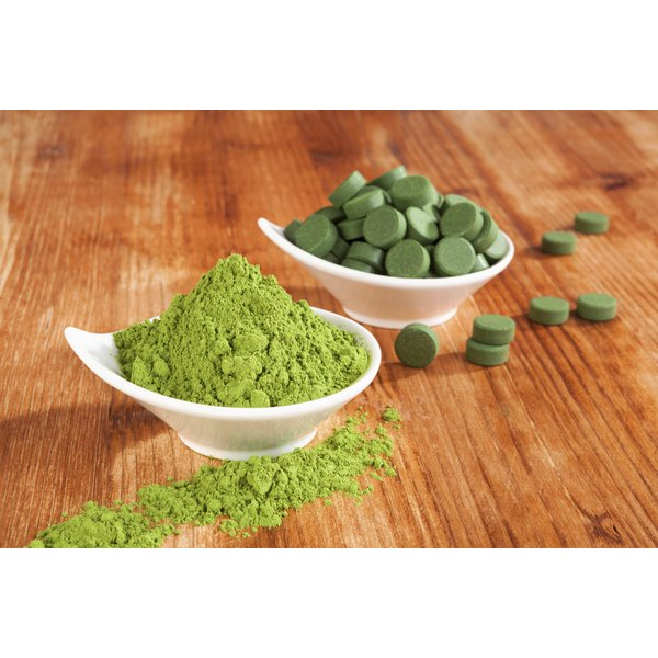 Spirulina tablets and powder in white bowls.