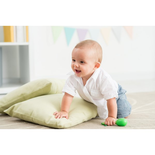 A smiling baby crawls on a sofa.