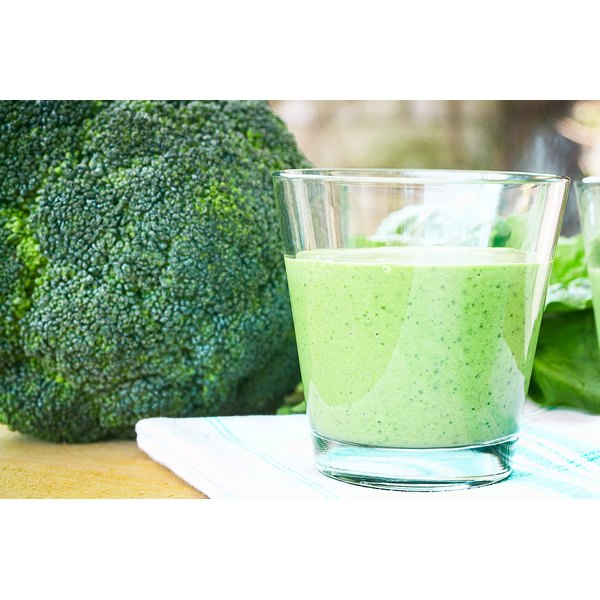 A green smoothie on the counter with a head of broccoli.