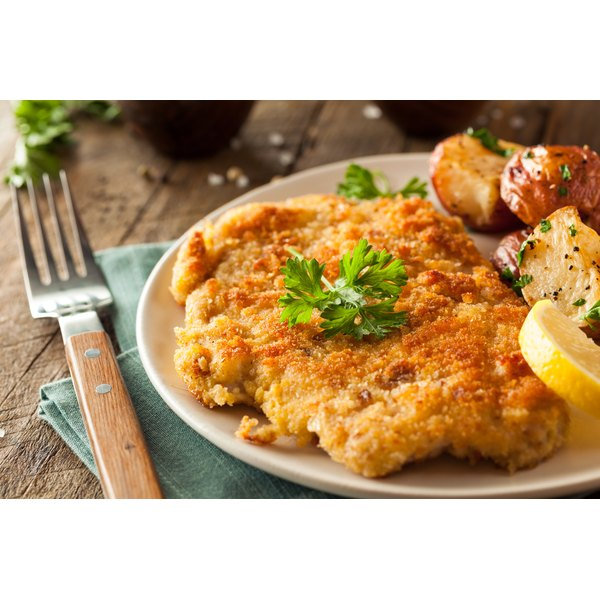 A breaded veal cutlet is served on a plate.