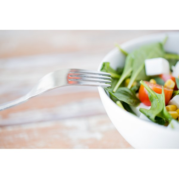 A close-up of a fork and a bowl of spinach salad.