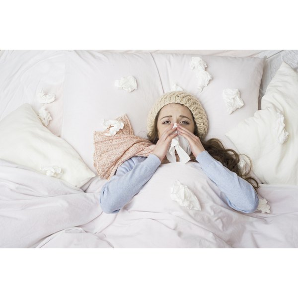 A woman sick in bed with tissues all around her.