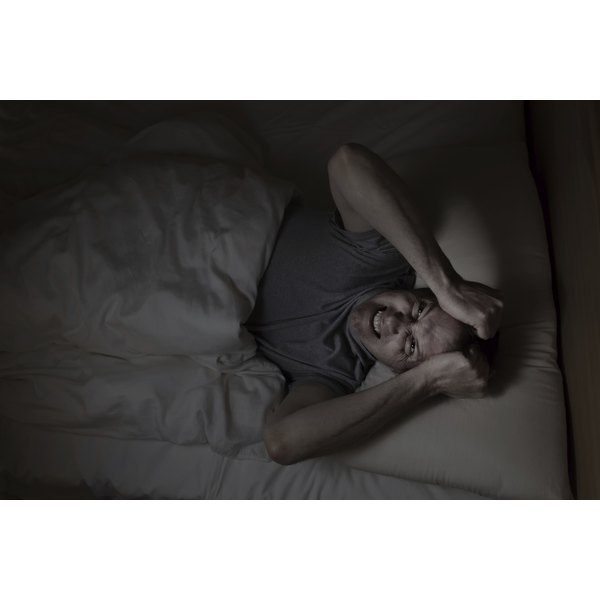 A man in bed holds his head as he has trouble sleeping.