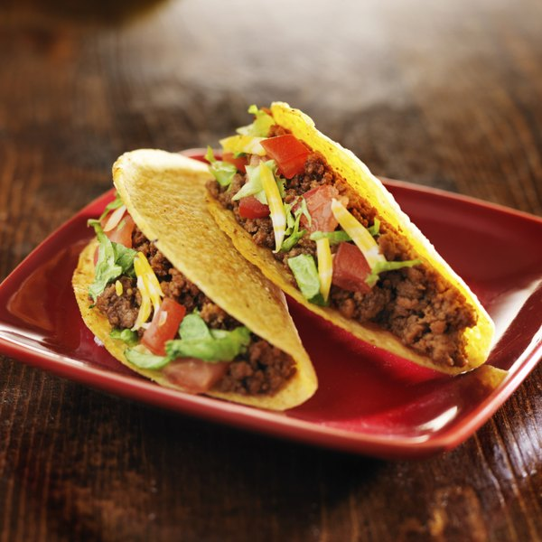 Two hard shell beef tacos on a plate.