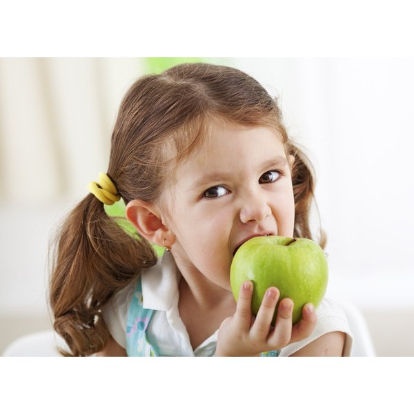 young girl biting into apple