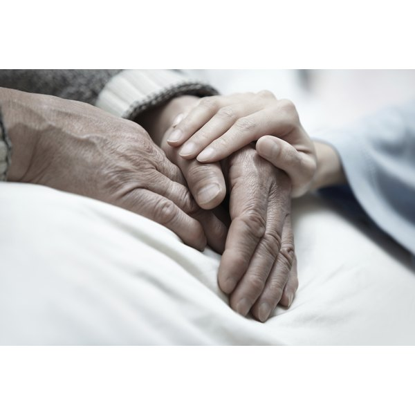 Woman's hand on senior man's hands in a hospital bed