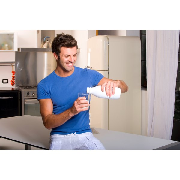 A man pours himself a glass of mlik in the kitchen while sitting on the counter.