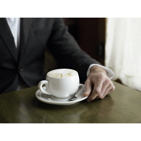 A cup of coffee on a table beside a man's hand.