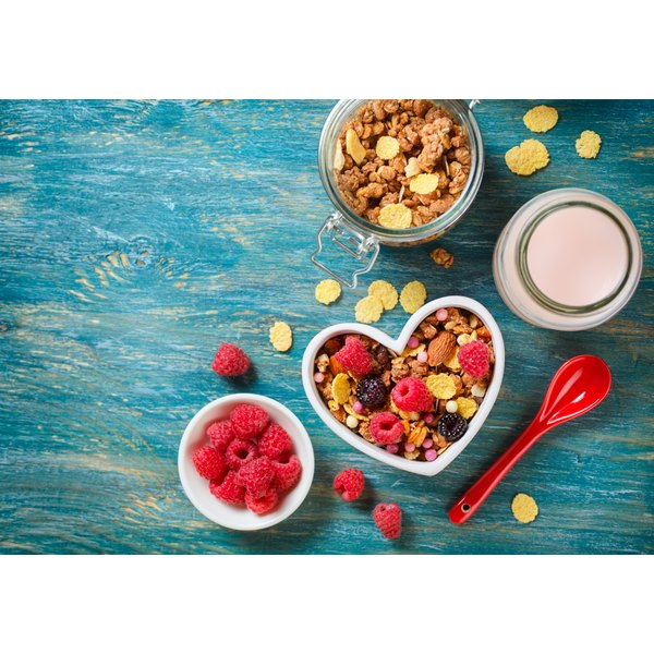 A heart shaped bowl with healthy cereal, berries and milk.