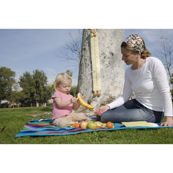 A mother and daughter having a picnic in the park near a growth chart.