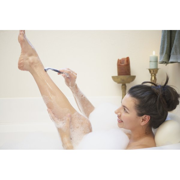 A woman is shaving her legs.
