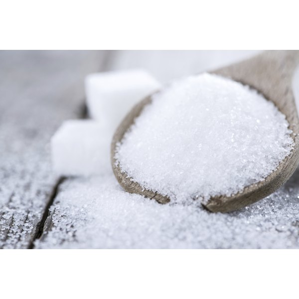 A wooden spoon filled with white sugar spills onto a table in front of sugar cubes.