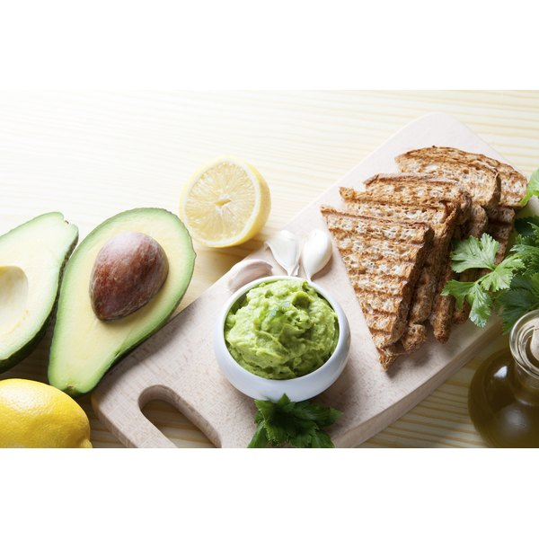 An avocado snack of guacamole and whole grain toast on the kitchen counter.