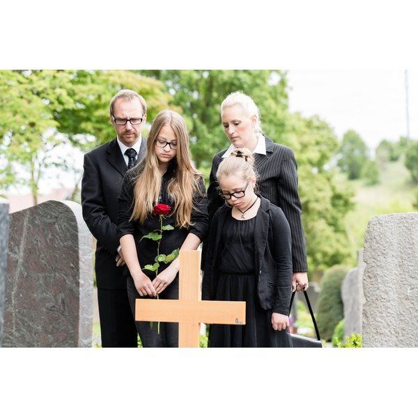 Two children at a gravesite with their parents, dressed in black.
