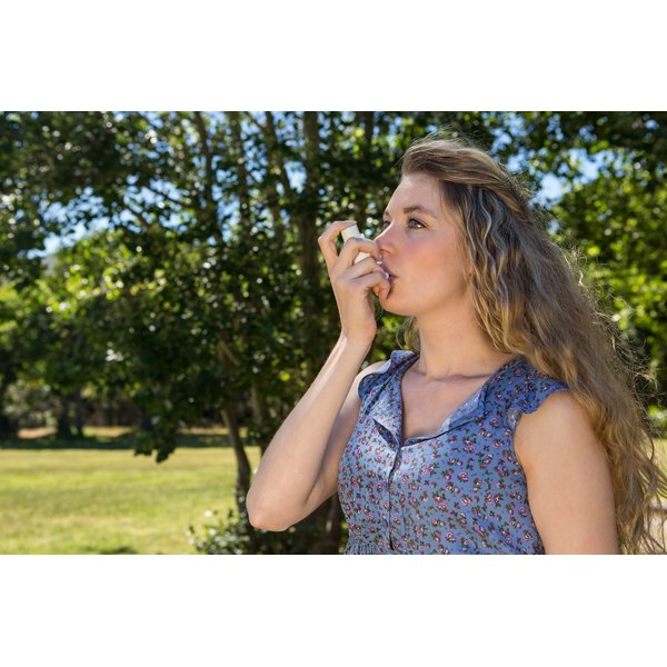 A young woman is using an inhaler.