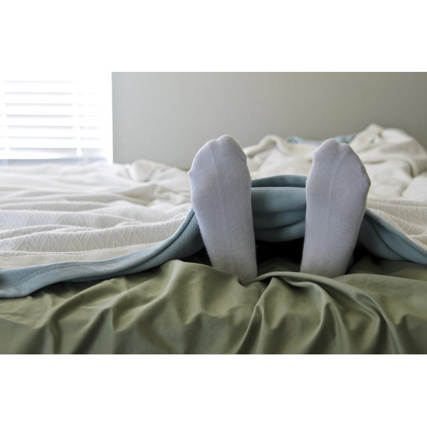 Feet wearing socks sticking out from the covers.