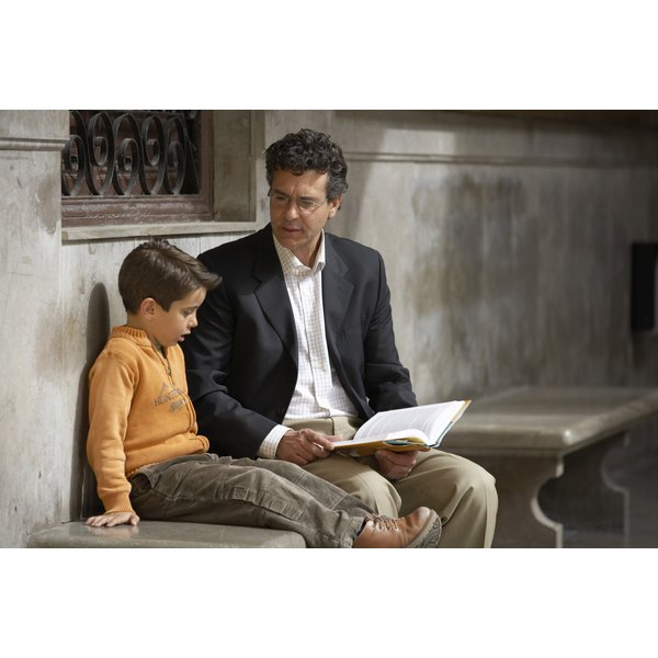 Father and his young son sit on a bench and talk while the dad has a book open.