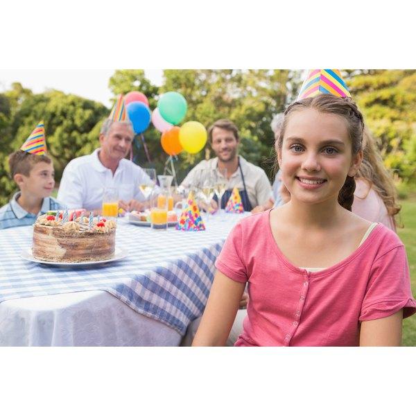 Girl having birthday cake with her family outside