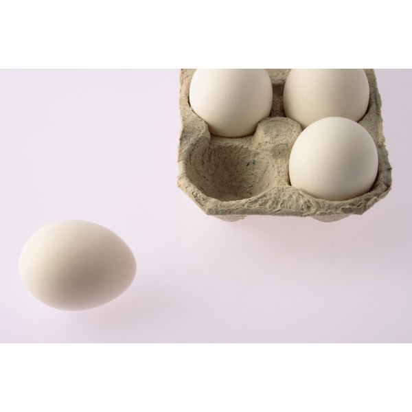 Aerial view of eggs in carton, one on table.