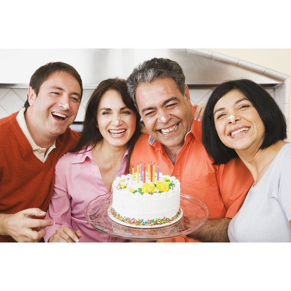 Man with friends and cake laughing.