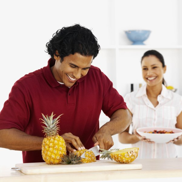 A young man slicing pineapple on a cutting board.