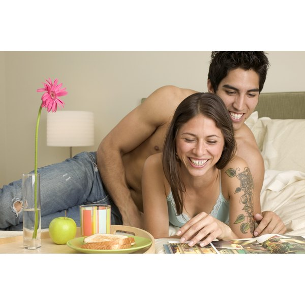 A couple smiling while looking at a magazine and eating breakfast on the bed.