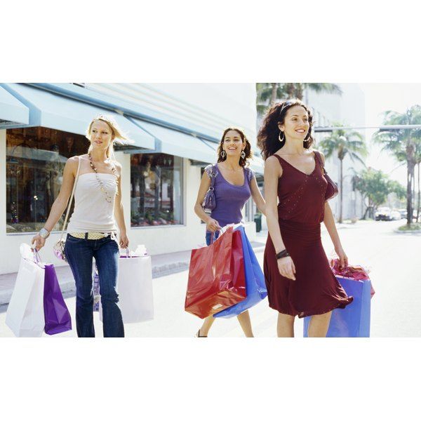 Women walking with hands full of shopping bags.