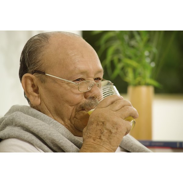 A middle-aged man drinks a glass of water.