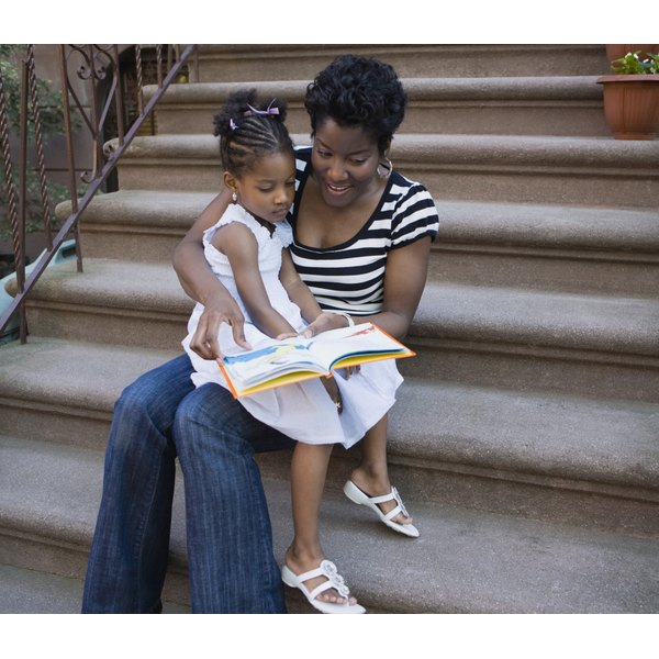 A mother reads a book to her daughter while sitting on a stoop.
