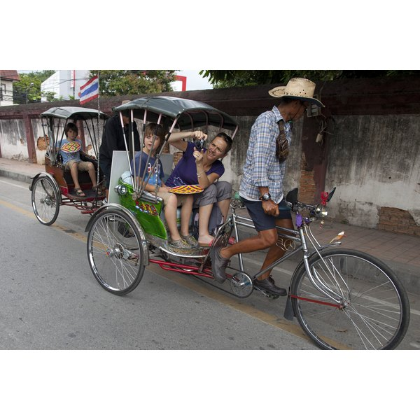 French tourists riding in rickshaws in Thailand.